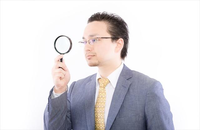虫眼鏡で何かを調べている男性